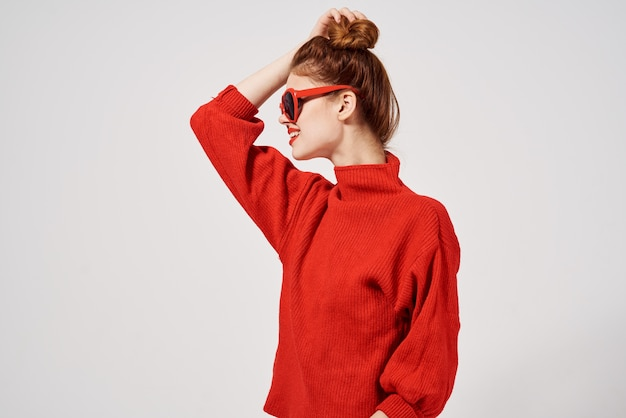 Modelo de mulher elegante com suéter vermelho e óculos de sol gesticulando Foto Premium