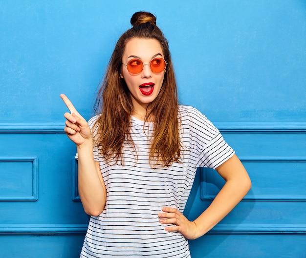 Modelo de mulher em roupas de verão casual com lábios vermelhos, posando perto de parede azul. tem uma boa ideia de como melhorar o projeto, levantar o dedo, querer soar e expressar pensamentos Foto gratuita