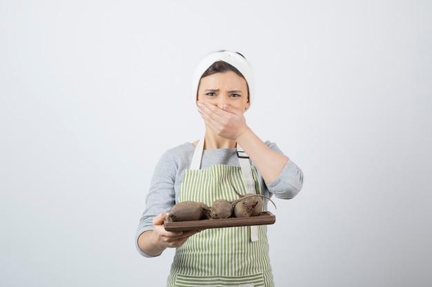 Modelo de mulher jovem e bonita no avental com uma placa de madeira de beterraba cobrindo a boca. Foto gratuita