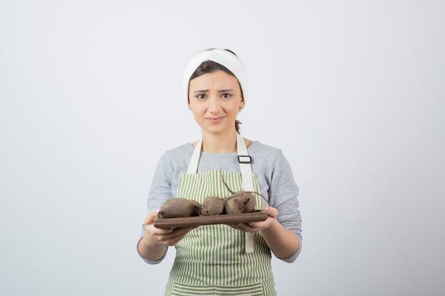 Modelo de mulher jovem e bonita no avental segurando uma placa de madeira com beterraba. Foto gratuita