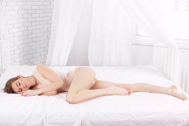 Modelo de mulher jovem sexy deitada na cama Foto Premium