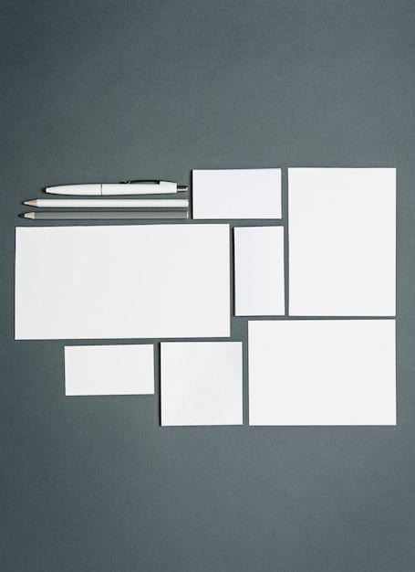 Modelo de negócios com cartões, papéis, caneta. espaço cinza. Foto gratuita