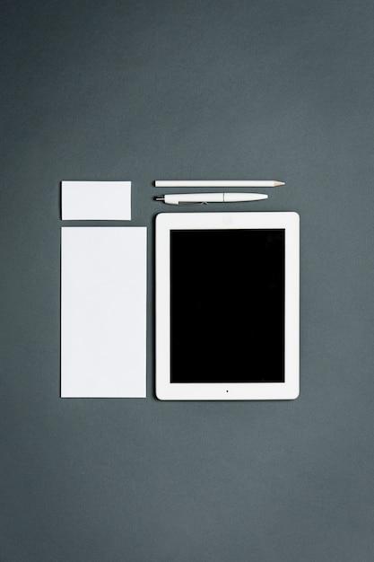 Modelo de negócios com cartões, papéis, tablet. espaço cinza. Foto gratuita