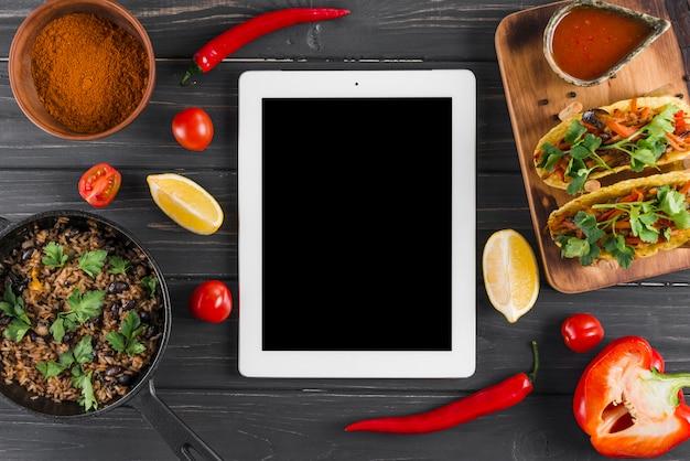 Modelo de tablet plana leigos com comida mexicana Foto gratuita