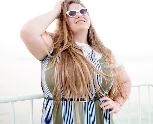 Modelo de tamanho grande usando óculos escuros Foto gratuita