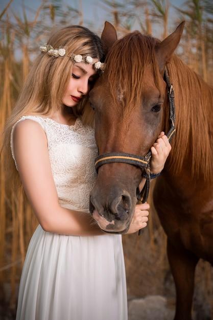 Modelo de vestido branco, posando com um cavalo Foto gratuita
