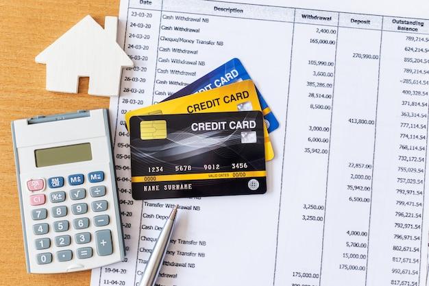 Modelo e calculadora da casa no extrato bancário e no cartão de crédito em uma tabela de madeira. conceito de hipoteca de compra de casa Foto Premium