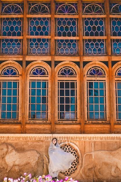 Modelo em roupas de oração em frente a uma mesquita histórica Foto gratuita