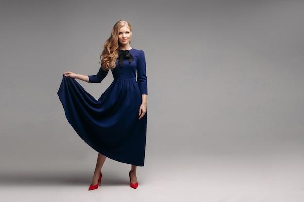 Modelo esbelto deslumbrante em vestido azul brilhante e salto preto. Foto Premium