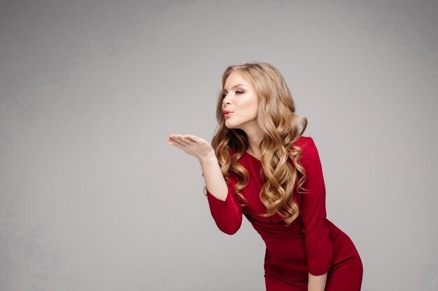 Modelo esbelto deslumbrante em vestido vermelho brilhante e salto preto. Foto Premium