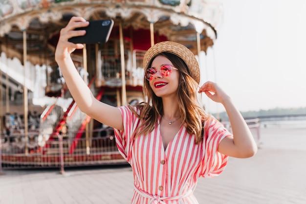 Modelo feminino alegre em traje listrado, posando perto de carrossel com chapéu de palha. tiro ao ar livre da elegante garota caucasiana usando smartphone para selfie no parque de diversões. Foto gratuita