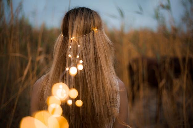 Modelo feminino com contas de cabelo de iluminação na natureza Foto gratuita