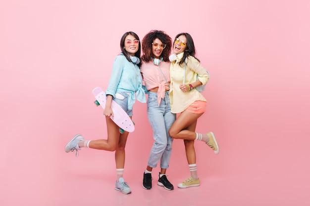 Modelo feminino de cabelos negros entusiasmados com lindo bronzeado em pé em uma perna enquanto seus amigos sorriem. alegre mulher africana em jeans e sapatos pretos, se passando perto da garota skatista de camisa azul. Foto gratuita