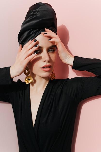 Modelo feminino elegante com turbante olhando para a câmera Foto gratuita