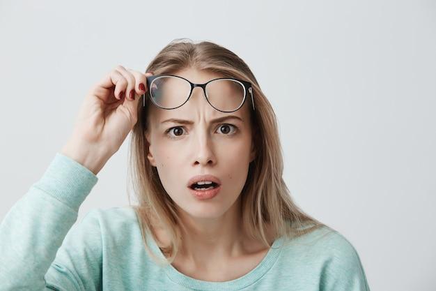 Modelo feminino jovem surpreso com longos cabelos loiros, usa óculos e camisa de mangas compridas azul, parece com terror Foto gratuita