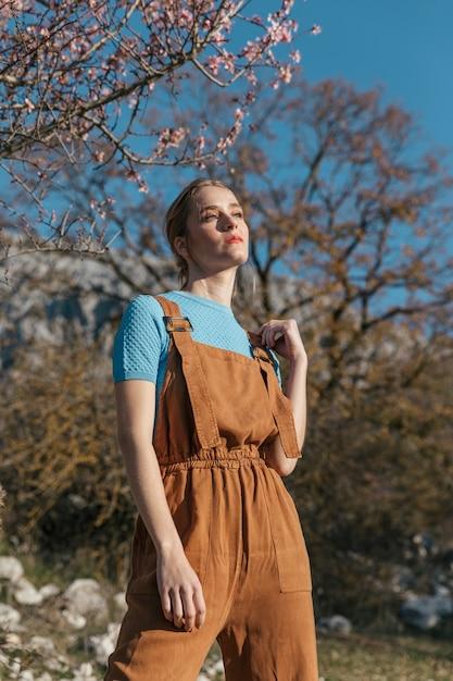 Modelo feminino posando sob a árvore de florescência Foto gratuita