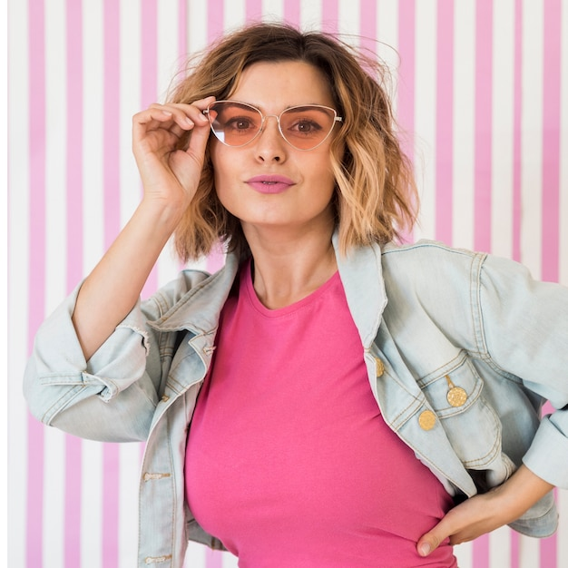 Modelo feminino usando óculos cor de rosa Foto gratuita