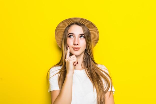 Modelo fofo em camiseta branca e chapéu entre fundo laranja com carinha engraçada Foto gratuita