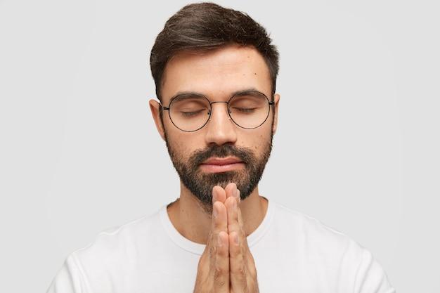 Modelo jovem barbudo focado mantém as palmas das mãos em gesto de oração, acredita na boa sorte. Foto gratuita