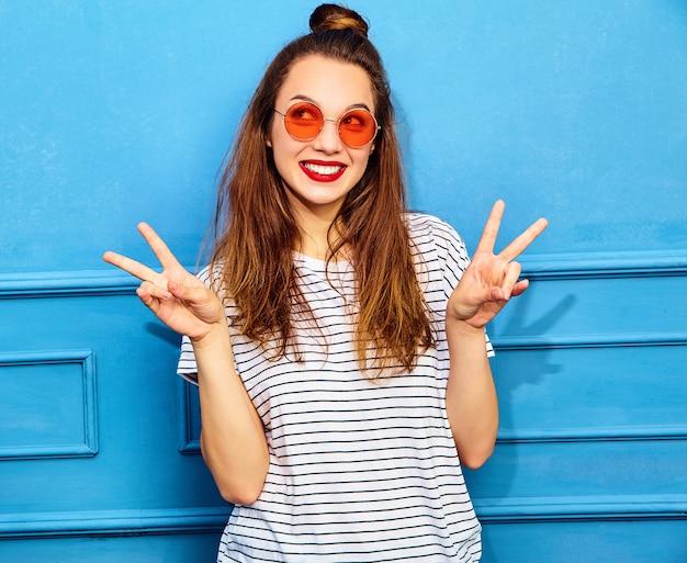 Modelo jovem elegante em roupas de verão casual com lábios vermelhos, posando perto da parede azul. mostrando sinal de paz Foto gratuita