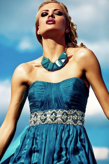 Modelo jovem mulher loira sexy vestido de noite posando no fundo do céu azul Foto gratuita