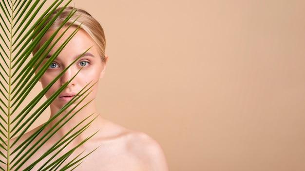 Modelo loiro close-up atrás de uma planta com cópia-espaço Foto gratuita