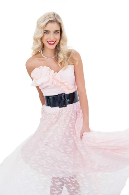 Modelo loiro satisfeito no vestido rosa posando agitando seu vestido Foto Premium