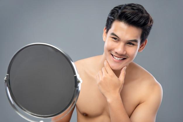 Modelo masculino asiático com confiança, olhando-se no espelho Foto Premium
