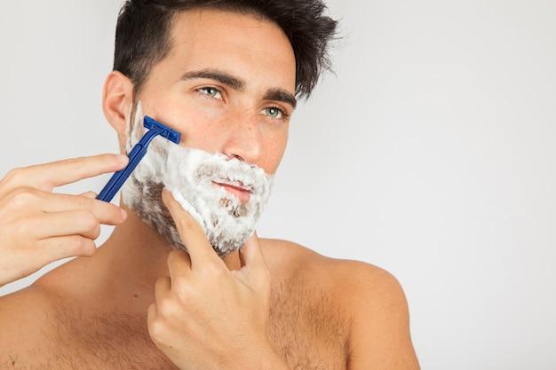 Modelo masculino, barbeando a barba Foto gratuita