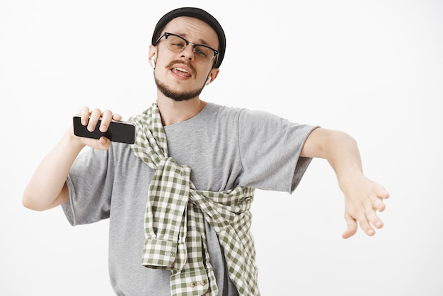 Modelo masculino bonito, carismático e descontraído, com barba em óculos e gorro hipster dançando com as mãos abertas, expressão despreocupada ouvindo música em fones de ouvido sem fio segurando um smartphone Foto gratuita