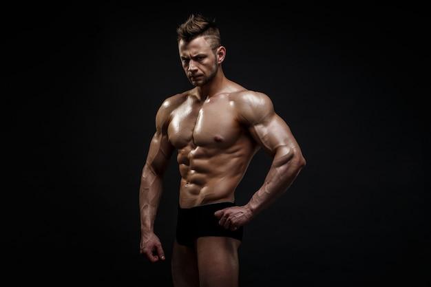 Modelo masculino considerável que levanta no estúdio na frente de um fundo preto. Foto Premium