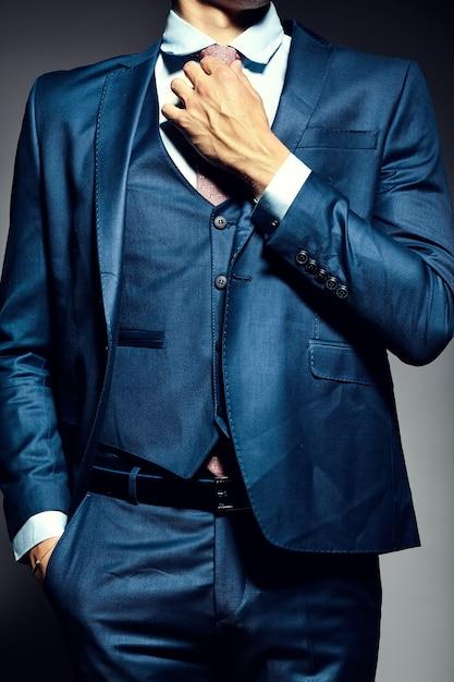 Modelo masculino jovem empresário bonito elegante de terno amarrar a gravata Foto gratuita