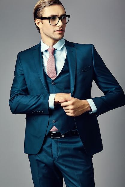 Modelo masculino jovem empresário bonito elegante de terno e óculos da moda, posando no estúdio Foto gratuita