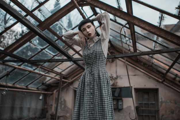 Modelo moreno gótico de vestido. moda vitoriana. modelo gótico em fundo grunge. misteriosa mulher morena com estrondo. modelo de vestido em fundo abandonado. roupas da moda. vampiro misterioso Foto Premium