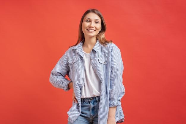 Modelo muito feminino, posando com uma expressão de rosto sorridente na parede vermelha Foto gratuita