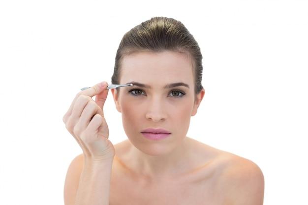 Modelo natural concentrado de cabelos castanhos arrancando as sobrancelhas Foto Premium