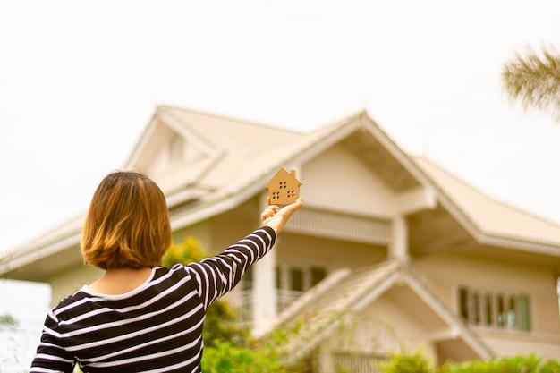 Modelo pequeno em casa na mão da mulher frente uma casa. Foto Premium
