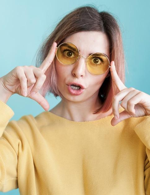 Modelo posando com óculos em estúdio Foto gratuita