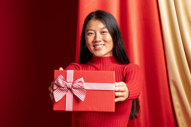 Modelo segurando a caixa de presente para o ano novo chinês Foto gratuita