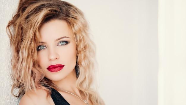 Modelo sensual com cabelos loiros ondulados e lábios vermelhos olhando Foto Premium