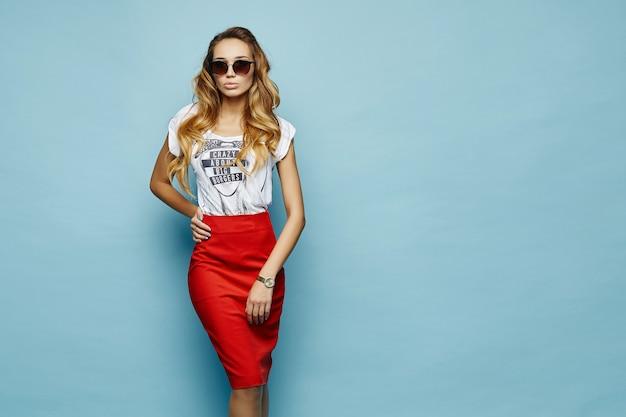 Modelo sensual em uma saia vermelha com uma camiseta elegante Foto Premium