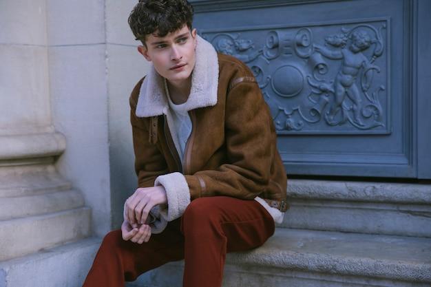 Modelo sentado na porta da frente, olhando para os lados Foto gratuita