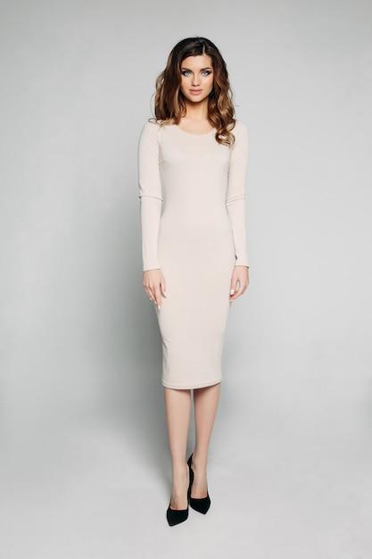 Modelo slim com cabelos ondulados morena posando em vestido de marfim e salto preto. Foto Premium