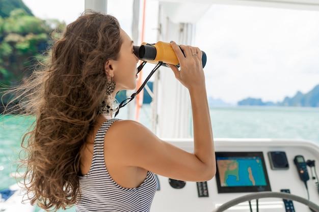 Modelo vestindo vestido listrado e segurando binóculos Foto Premium