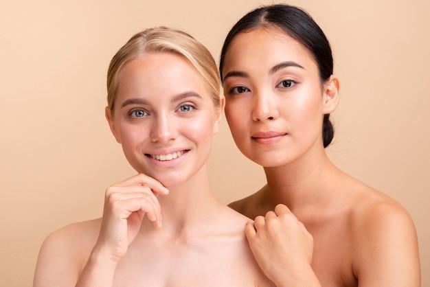 Modelos caucasianos e asiáticos de close-up posando juntos Foto gratuita