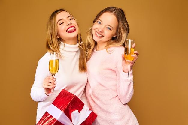 Modelos com grande caixa de presente bebendo champanhe em copos comemorando o ano novo Foto gratuita