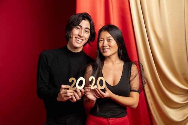 Modelos posando com sinal de ano novo Foto gratuita