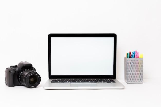Modern laptop e câmera no fundo branco Foto gratuita