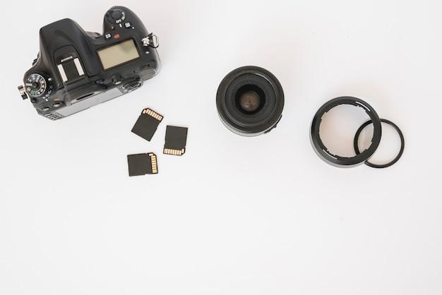 Moderna câmera dslr; cartões de memória e lente da câmera com anéis de extensão em pano de fundo branco Foto gratuita