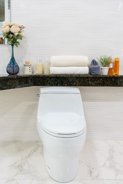 Moderna espaçosa casa de banho com azulejos brilhantes com vaso sanitário e pia Foto Premium